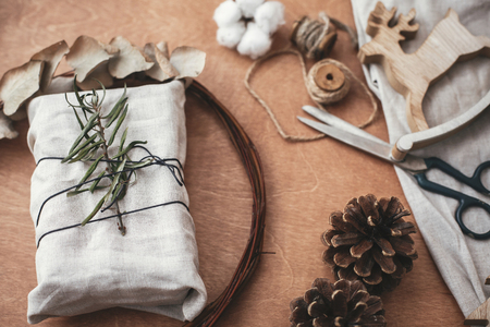 Photo pour Stylish rustic gift wrapped in linen fabric with green branch on wooden table with pine cones,wreath,tree, reindeer, scissors, twine, cotton. Simple eco presents plastic free. Zero waste holidays - image libre de droit