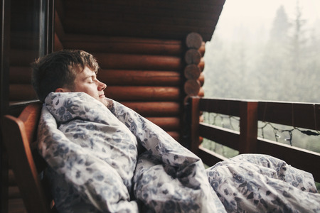 Photo pour Happy traveler man resting in blanket on wooden porch with view  on woods and mountains. Space for text. Hipster relaxing in wooden cabin in forest. Travel and vacations. - image libre de droit