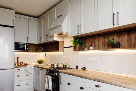 Foto für Stylish kitchen interior design. Luxury modern kitchen furniture in grey color and steel oven,fridge, sink, wooden tabletop, pots,. Gray cabinets in scandinavian style. Home renovation. - Lizenzfreies Bild