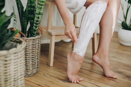 Photo pour Hair Removal concept, depilation process. Young woman in white towel applying shaving cream on her legs and holding holding plastic razor in home bathroom with green plants. Skin care - image libre de droit