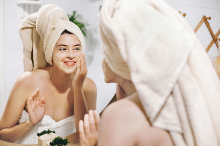 Foto de Skin Care concept. Young happy woman in towel making facial massage with organic face scrub and looking at mirror in stylish bathroom. Girl applying scrub cream, peeling and cleaning skin - Imagen libre de derechos