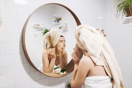 Foto de Young happy woman in towel making facial massage with  organic face scrub and looking at mirror in stylish bathroom. Girl applying scrub cream, peeling and cleaning skin. Skin Care - Imagen libre de derechos