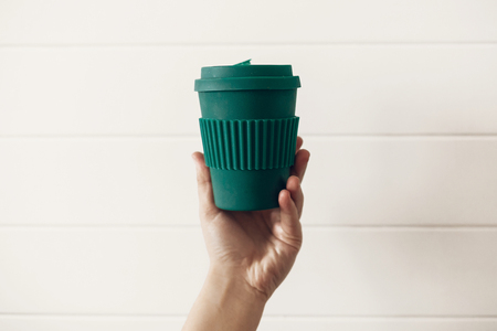 Photo pour Zero waste concept. Hand holding stylish reusable eco coffee cup on white wooden background. Green Cup from natural  bamboo fiber. Ban single use plastic. Make a choice. - image libre de droit