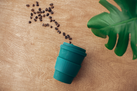 Foto de Stylish reusable eco coffee cup  on wooden background with roasted coffee beans and green monstera leaf. Ban single use plastic, zero waste concept, flat lay. Sustainable lifestyle. - Imagen libre de derechos