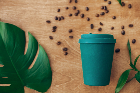 Photo pour Stylish reusable eco coffee cup  on wooden background with roasted coffee beans and green monstera leaf. Ban single use plastic, zero waste concept, flat lay. Sustainable lifestyle. - image libre de droit