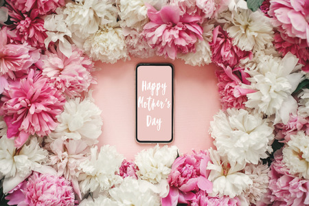 Photo for Happy Mother's Day text sign on screen phone with pink and white peonies on pastel pink paper, flat lay. Stylish floral greeting card. - Royalty Free Image
