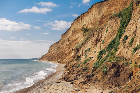 Photo for Beautiful view of sandy cliff near sea beach. Landscape of beach cliff and waves. Summer vacation concept. Exploring interesting places - Royalty Free Image