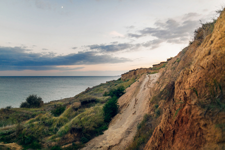 Photo for Beautiful view of sandy cliff near sea beach in sunset. Landscape of beach cliff and waves and cloudy sky in sunset or sunrise. Summer vacation concept. Exploring interesting places - Royalty Free Image