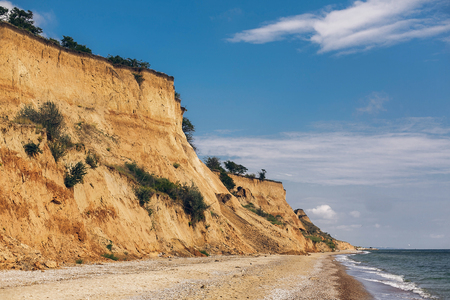 Photo for Beautiful view of sandy cliff near sea beach. Landscape of beach cliff and waves in sunny weather. Summer vacation concept. Exploring interesting places - Royalty Free Image