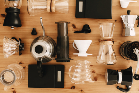 Foto de Kettle, scales, geyser, grinder, aeropress, pour over, glass flask top view. Alternative coffee brewing method set, flat lay. Stylish accessories and items for alternative coffee on wooden table. - Imagen libre de derechos