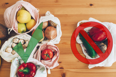 Foto de Ban single use plastic. Zero Waste shopping concept. Fresh groceries in reusable eco bags and vegetables in plastic polyethylene bag on wooden table. Choose plastic free items. - Imagen libre de derechos