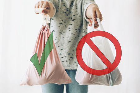Foto de Ban single use plastic, stop sign. Choose plastic free. Zero Waste shopping concept. Woman holding in one hand groceries in reusable eco bag and in other vegetables in plastic polyethylene bag - Imagen libre de derechos