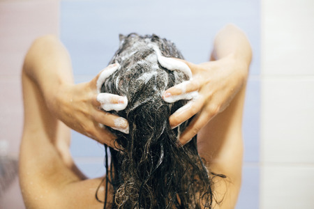 Foto de Young happy woman washing her hair with shampoo, hands with foam closeup. Back of beautiful brunette girl taking shower and enjoying relax time. Body and hair hygiene, lifestyle concept - Imagen libre de derechos
