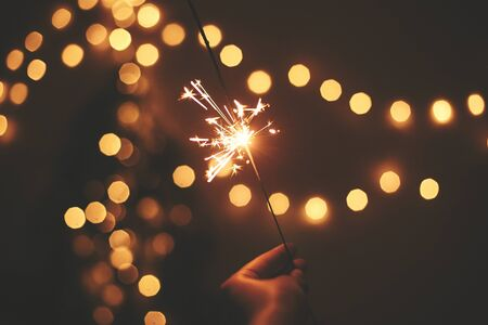 Photo pour Happy New Year. Glowing sparkler in hand on background of golden christmas tree lights, celebration in dark festive room. Space for text.   Fireworks burning in hand. Happy Holidays - image libre de droit