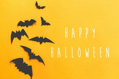 Photo pour Happy Halloween text, greeting card. Black bats flying on bright yellow paper background. Flat lay. Modern spooky minimal halloween decor. Halloween sign - image libre de droit