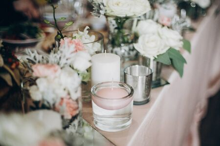 Photo pour Candle, White  flowers in modern glass vase on pink centerpiece. Stylish luxury decor on wedding table.Luxury catering and adorning. Holiday feast - image libre de droit