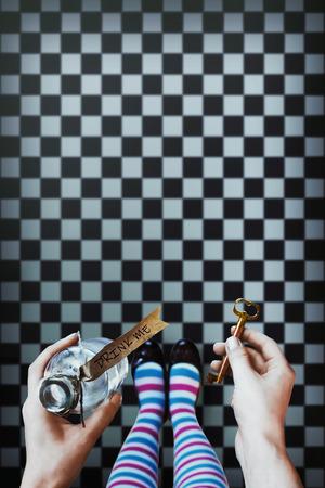 Foto de Alice in wonderland. Background. A key and a potion in hands against a chess floor - Imagen libre de derechos