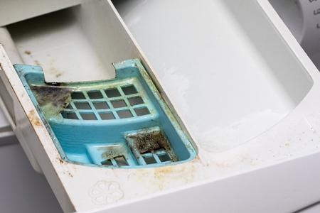 Foto de Dirty mouldy washing machine detergent and fabric conditioner dispenser drawer. Mold and dirt in washing machine. - Imagen libre de derechos