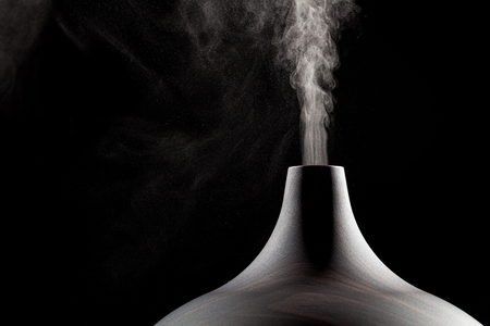 Foto de Close up of an ultrasonic aromatherapy oil diffuser in use. Atomized water droplets being dispensed into the air. - Imagen libre de derechos