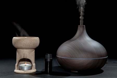 Foto de Aromatherapy. Traditional and modern oil burner and aroma diffuser working with essential oil bottle. Image comparing methods. - Imagen libre de derechos