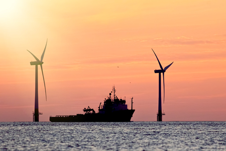 Photo for Sustainable resources. Wind farm with ship silhouette at tropical sunrise or sunset. Solar and wind energy and food supply represented in this tranquil image with copy space. - Royalty Free Image