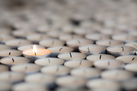 Foto de Shining light from a solitary burning candle flame. Selective focus on one flaming tealight among many extinguished candles.   - Imagen libre de derechos