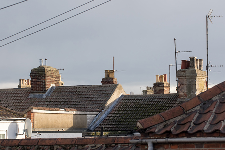 Foto de Northern town tiled roof tops with chimneys and aerials UK. Cramped urban working class housing. Old town building rooves. - Imagen libre de derechos