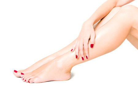 Photo pour Beautiful well-groomed female legs with red pedicure isolated on white background - image libre de droit