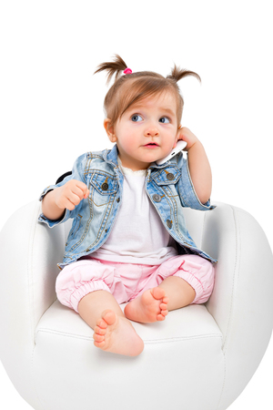 Foto de Portrait of a beautiful baby girl, talking on the phone, isolated on white background - Imagen libre de derechos