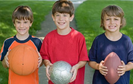 Three Boys Holding Sports Balls
