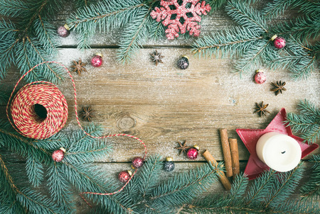 Photo for Christmas decorations: fur-tree branches, colorful glass balls, a candle, red glittering snowflacke, cinnamon sticks and anise stars on a rough wooden background with a copy space - Royalty Free Image
