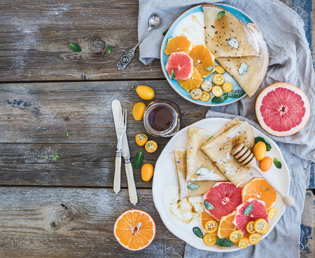 Photo pour Spring vitamin breakfast set. Thin crepes or pancakes with fresh grapefruit, orange, kumquat, honey, cream and mint leaves over a rustic wood background, top view - image libre de droit