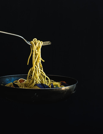 Photo for Hot spaghetti with tomatoes in cooking pan and fork on black background - Royalty Free Image