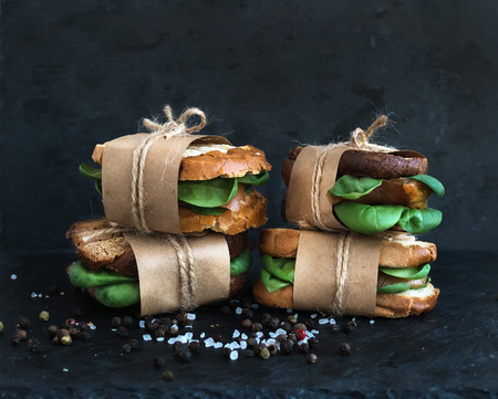 Photo for Cured chicken and spinach whole grain sandwiches placed one on another wrapped in craft paper and tied with a decoration rope  with spices and black stone background - Royalty Free Image