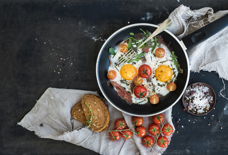 Photo pour Pan of fried eggs, bacon and cherry-tomatoes with bread on dark table surface, top view - image libre de droit