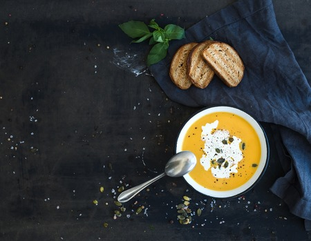 Photo for Pumpkin soup with cream, seeds, bread and fresh basil in rustic metal plate on grunge black background. Top view, copy space - Royalty Free Image