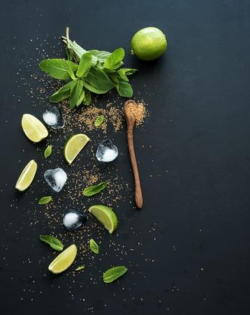 Foto de Ingredients for mojito. Fresh mint, limes, ice, sugar over black backdrop. Top view, copy space - Imagen libre de derechos