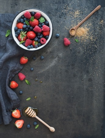 Photo for Strawberries, raspberries, blueberries and mint leaves, honey, cane sugar, dark grunge background, top view, copy space - Royalty Free Image