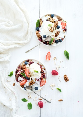 Photo pour Healthy breakfast. Berry crumble with fresh blueberries, raspberries, strawberries, almond, walnuts, pecans, yogurt, and mint in ceramic plates over white wooden surface, top view - image libre de droit