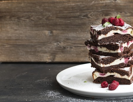 Foto de Brownies-cheesecake tower with raspberries on white ceramic plate, wooden backdrop, copy space - Imagen libre de derechos