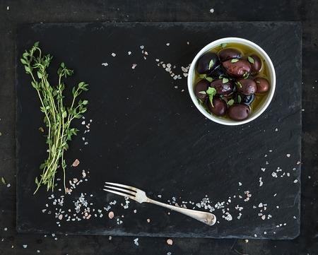 Foto de Food frame on dark stone surface. Mediterranean olives in oil, fresh thyme, spices. Top view, copy space in the center - Imagen libre de derechos