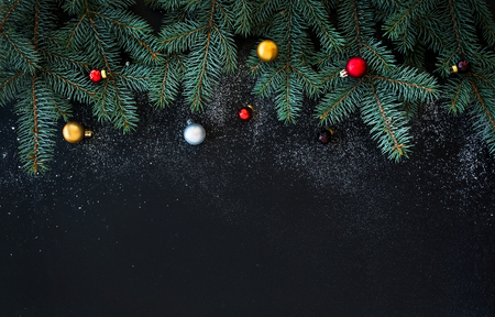 Foto de Christmas or New Year decoration background: fur-tree branches, colorful glass balls  on black grunge background with copy space - Imagen libre de derechos