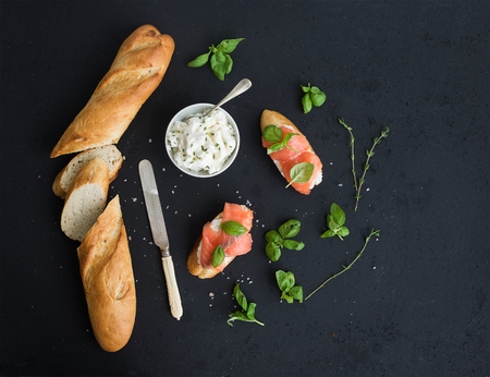 Photo for Salmon, ricotta and basil sandwiches with baguette over black grunge background. Top view, copy space - Royalty Free Image