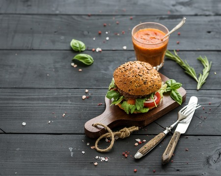 Photo pour Fresh homemade burger on dark serving board with spicy tomato sauce, sea salt and herbs over dark wooden background, copy space - image libre de droit