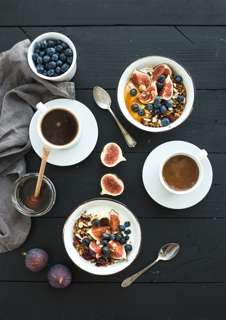 Photo for Healthy breakfast set. Bowls of oat granola with yogurt, fresh blueberries and figs, coffee, honey, over black wooden backdrop. Top view - Royalty Free Image
