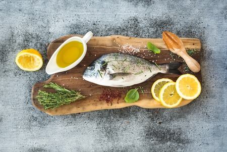 Foto de Fresh uncooked dorado or sea bream fish with lemon, herbs, oil and spices on rustic wooden board over grunge backdrop, top view - Imagen libre de derechos