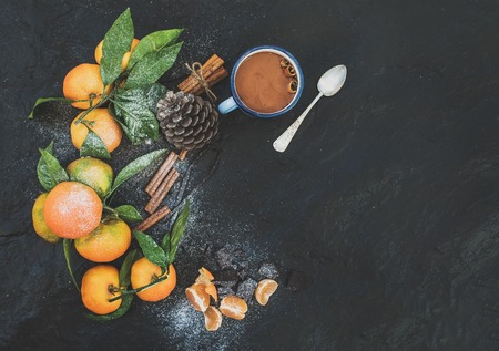 Photo for Christmas or New Year frame. Fresh mandarines with leaves, cinnamon sticks, vanilla, pine cone and mug of hot chocolate over dark stone background, top view, copy space - Royalty Free Image