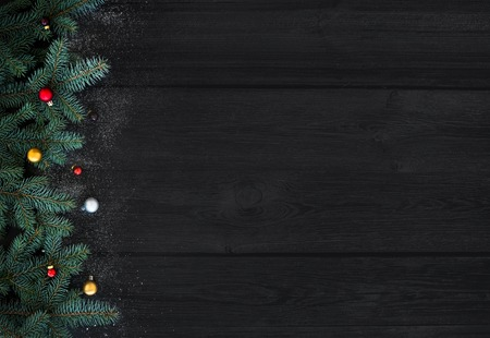 Photo for Christmas or New Year decoration background: fur-tree branches, colorful glass balls on black wood background with copy space - Royalty Free Image