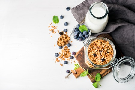 Photo pour Healthy breakfast ingrediens. Homemade granola in open glass jar, milk or yogurt bottle, blueberries and mint on white wooden background, top view, copy space - image libre de droit