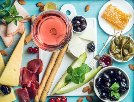 Foto de Summer wine snack set. Glass of rose, meat, cheese, olives, honey, bread sticks, nuts, capers and berries with white ceramic board in center, blue wooden background, top view - Imagen libre de derechos
